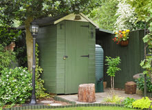 An English Back garden. Scene with Shed and Pet cat sitting amongst the foliage Royalty Free Stock Images