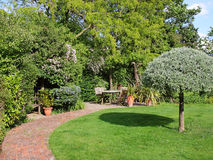 An English Back garden. Scene with patio and seating area Stock Image