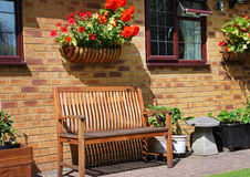 An English back Garden seat. English back Garden with wooden benach seat and flower filled basket of Begonias on the wall Stock Photo