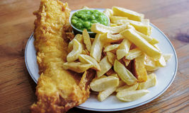 English battered Cod Fish and Chips with Mushy Peas in a plate. Delicious deep fried battered Cod Fish with Chips in a Fish and Chips restaurant in Greater Royalty Free Stock Images