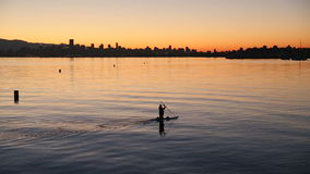 English Bay Dawn Paddle. A paddler does an early morning workout in English Bay in front of the downtown Vancouver skyline. British Columbia, Canada stock video