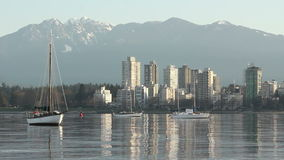 English Bay Morning, Vancouver. Anchored sailboats bob gently on English Bay in the morning. The apartments of the West End catch the suns first morning rays stock footage