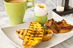 English breakfast. An English breakfast - soft boiled egg, fried bacon, toasts and coffee Stock Image