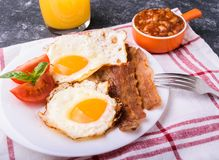 English breakfast - bacon, eggs. English breakfast - bacon, fried eggs, beans and orange juice. Served on white plate with sliced tomato and basil leaves. Dark Stock Images