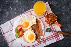 English breakfast - bacon, eggs. English breakfast - bacon, fried eggs, beans and orange juice. Served on white plate with sliced tomato and basil leaves. Dark Royalty Free Stock Photography