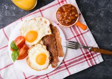 English breakfast - bacon, eggs. English breakfast - bacon, fried eggs, beans and orange juice. Served on white plate with sliced tomato and basil leaves. Dark Stock Photography