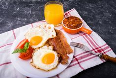 English breakfast - bacon, eggs. English breakfast - bacon, fried eggs, beans and orange juice. Served on white plate with sliced tomato and basil leaves. Dark Stock Photo