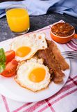English breakfast - bacon, eggs. English breakfast - bacon, fried eggs, beans and orange juice. Served on white plate with sliced tomato and basil leaves. Dark Royalty Free Stock Image