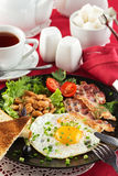 English breakfast with bacon, fried egg and beans Stock Photography