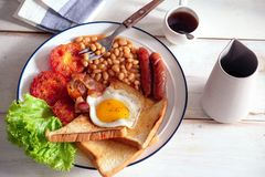 An English breakfast is a breakfast meal that typically includes bacon, sausages, eggs .. A full breakfast is a breakfast meal that typically includes bacon Royalty Free Stock Images
