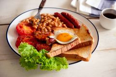 An English breakfast is a breakfast meal that typically includes bacon, sausages, eggs .. A full breakfast is a breakfast meal that typically includes bacon Royalty Free Stock Image