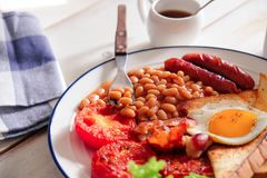 An English breakfast is a breakfast meal that typically includes bacon, sausages, eggs .. A full breakfast is a breakfast meal that typically includes bacon Stock Image