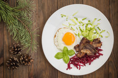 English breakfast in the Christmas of eggs, fried bacon and salad  grated boiled beet  cucumber. Wooden background. Top Stock Images