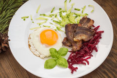 English breakfast in the Christmas of eggs, fried bacon and salad  grated boiled beet  cucumber. Wooden background. Top Royalty Free Stock Image