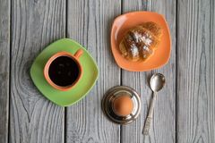 English breakfast, coffee with egg and croissant. Breakfast coffee egg and ruddy croissant view from above, on a wooden aged surface Royalty Free Stock Photo