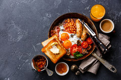 English Breakfast in cooking pan. With fried eggs, sausages, bacon, beans, toasts and coffee on dark stone background copy space Royalty Free Stock Images