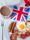 English Breakfast with cup of tea, toast and british flag. English fried breakfast on a white table top with cup of tea in union jack mug, buttered toast Royalty Free Stock Photos