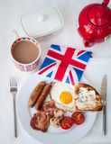 English Breakfast with cup of tea, toast and british flag. English fried breakfast on a white table top with cup of tea in union jack mug, buttered toast Stock Photo