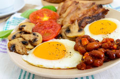 English breakfast: eggs, bacon, beans in tomato sauce, mushrooms, tomatoes, toast with cream cheese and a cup of coffee Royalty Free Stock Image