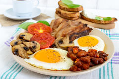 English breakfast: eggs, bacon, beans in tomato sauce, mushrooms, tomatoes, toast with cream cheese and a cup of coffee Royalty Free Stock Photo