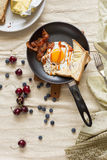 English breakfast - fried egg, bacon, bread blueberryand cherry Stock Images