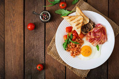 English breakfast - fried egg, beans, tomatoes, mushrooms, bacon and toast. Stock Photo