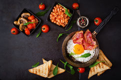 English breakfast - fried egg, beans, tomatoes, mushrooms, bacon and toast. Royalty Free Stock Images