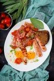 English breakfast - fried egg, sausage, tomatoes, bacon Stock Photos