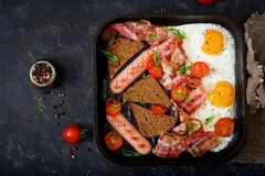 English breakfast - fried egg, sausage, tomatoes, bacon. And toast. Top view. Flat lay Royalty Free Stock Photo