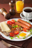 English breakfast with fried egg sausages bacon tomatoes beans Royalty Free Stock Photo