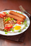 English breakfast with fried egg sausages bacon tomatoes beans Royalty Free Stock Image
