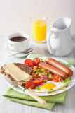 English breakfast with fried egg sausages bacon tomatoes beans Stock Images