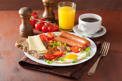 English breakfast with fried egg sausages bacon tomatoes beans Stock Photos