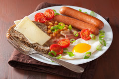 English breakfast with fried egg sausages bacon tomatoes beans Royalty Free Stock Photos