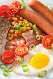 English breakfast with fried egg sausages bacon tomatoes beans Royalty Free Stock Photography