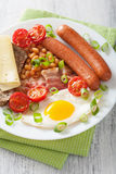 English breakfast with fried egg sausages bacon tomatoes beans Royalty Free Stock Images