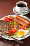 English breakfast with fried egg sausages bacon tomatoes beans Stock Photo