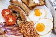 English breakfast with fried eggs, bacon, sausages, beans and toasts. Closeup Royalty Free Stock Images