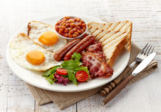 English breakfast. With fried eggs, bacon, sausages, beans, toasts and fresh salad Royalty Free Stock Photography