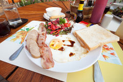 English breakfast. With fried eggs, bacon, sausages, toasts and fresh salad Stock Images