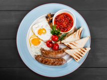 English breakfast - Fried eggs, beans, sausage, grilled tomatoes, mushrooms, toasted bread and sauce on plate. On dark wooden background. Healthy food, top view stock images