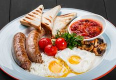 English breakfast - Fried eggs, beans, sausage, grilled tomatoes, mushrooms, toasted bread and sauce on plate. On dark wooden background. Healthy food, top view royalty free stock photo