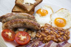English breakfast with fried eggs, sausages, beans, bacon and toasts on white wooden background,. Close-up Royalty Free Stock Photo