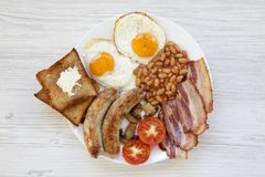 English breakfast with fried eggs, sausages, beans, bacon and toasts on white wooden background. Top view. Flat lay. From above, overhead Royalty Free Stock Image