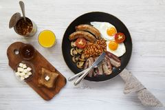 English breakfast in a frying pan with fried eggs, bacon, sausages, beans and toasts on white wooden background, top view. Flat la. Y. From above Stock Images