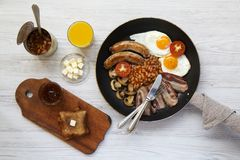 English breakfast in a frying pan with fried eggs, bacon, sausages, beans and toasts on white wooden background, top view. Flat la. Y. From above Stock Photography