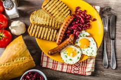 English breakfast - garlic toast, fried egg, beans and English breakfast, toast, egg, beans, sausages Royalty Free Stock Photo