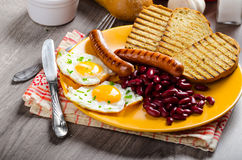 English breakfast - garlic toast, fried egg, beans and English breakfast, toast, egg, beans, sausages Royalty Free Stock Image