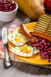 English breakfast - garlic toast, fried egg, beans and English breakfast, toast, egg, beans, sausages Stock Images