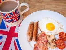 English breakfast with mug of tea and union jack flag. Full traditional cooked English breakfast with union jack mug of tea and British flag Royalty Free Stock Image